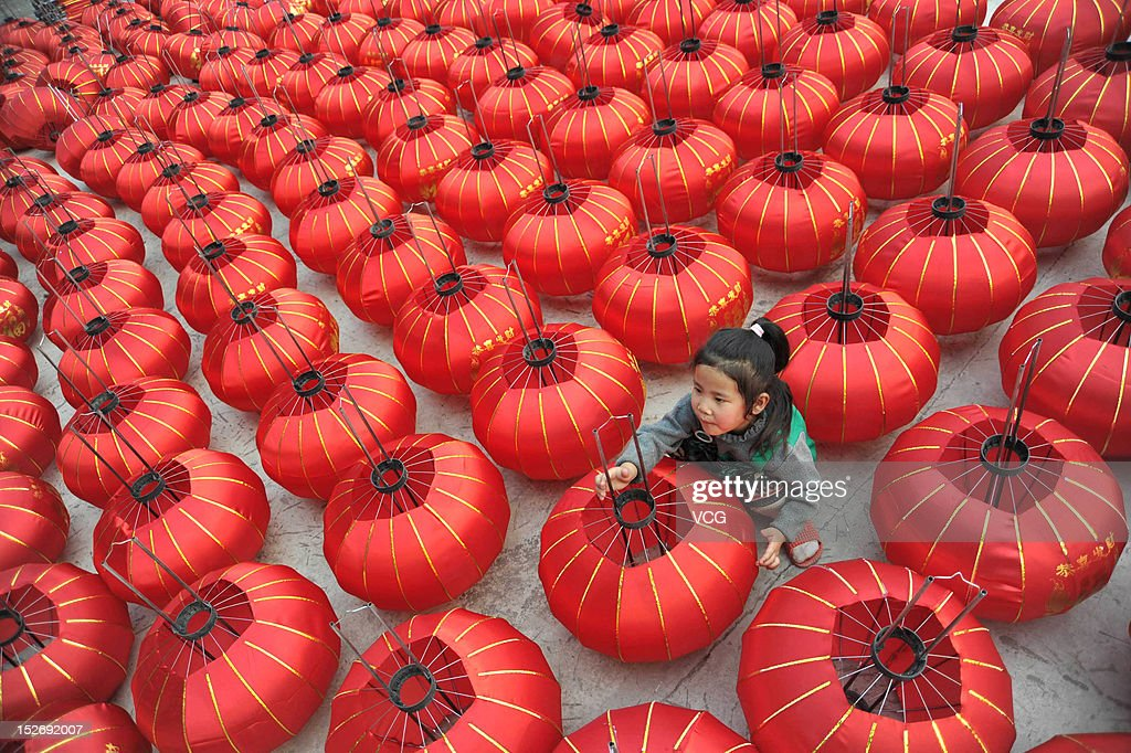 A child helps parents prepare red lanterns at a lantern workshop, in Zhao Village which is known as 'lantern village' before China's National Day on September 23, 2012 in Yuncheng, China. China's national day is celebrated every year on October 1.