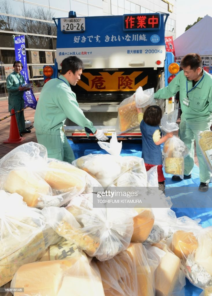 A child helps to load garbage bags onto the truck during a recycling lesson in the Kawasaki International Eco-Tech Fair 2013 in Kawasaki on February 2, 2013.