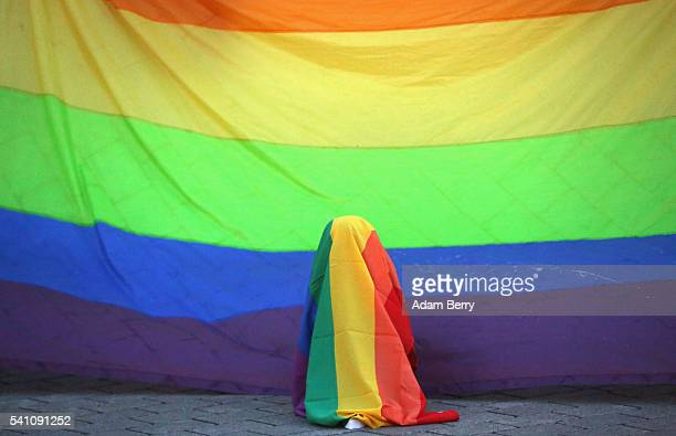 A child hides under a rainbow flag in front of a larger one hanging during a vigil for victims of a shooting at a gay nightclub in Orlando Florida...
