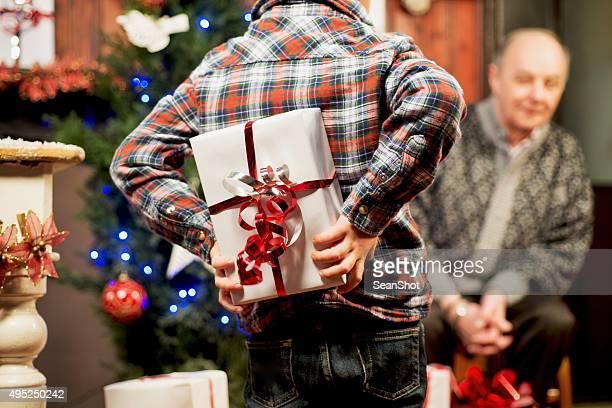 Child hiding a gift for Grandpa