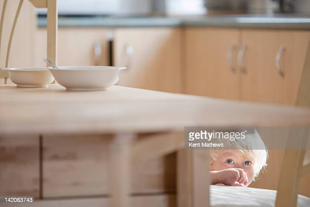 child hiding under kitchen table