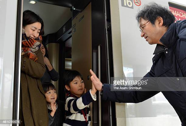 A child high fives with her grandfather at a Shinkansen platform at Akita Station on January 3 2015 in Akita Japan The return rush of the the New...