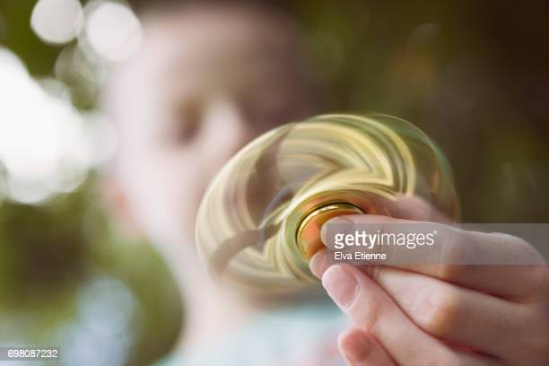 Child holding a moving fidget spinner