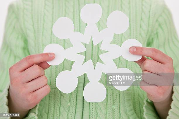 Child holding a paper snowflake