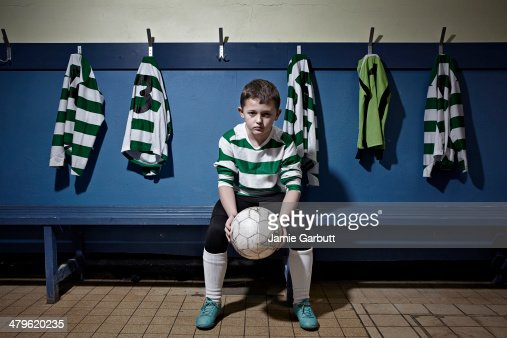 A child holding a soccer ball looking determined : Stock Photo