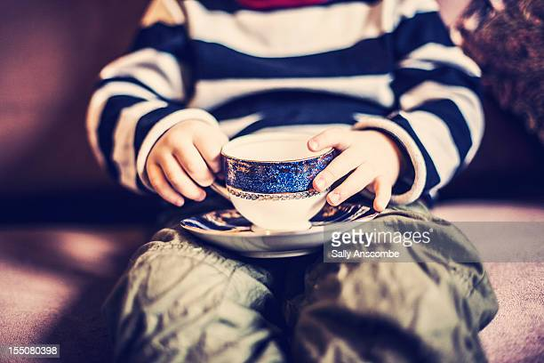 Child holding a tea cup and saucer.