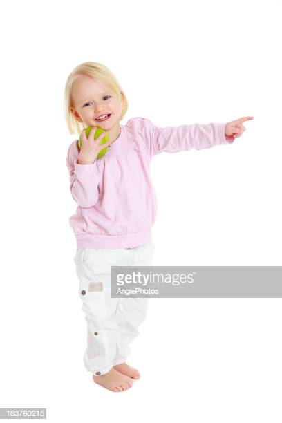 Child holding apple and pointing