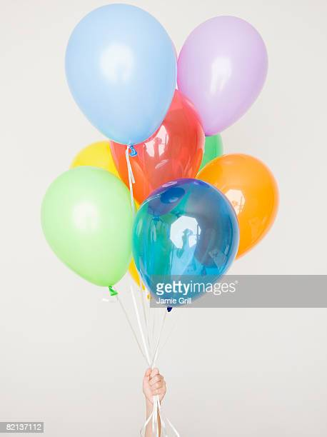 Child holding assorted balloons