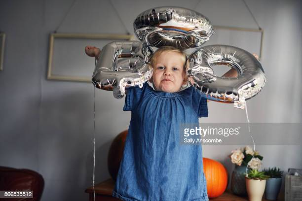 Child holding balloons that say boo