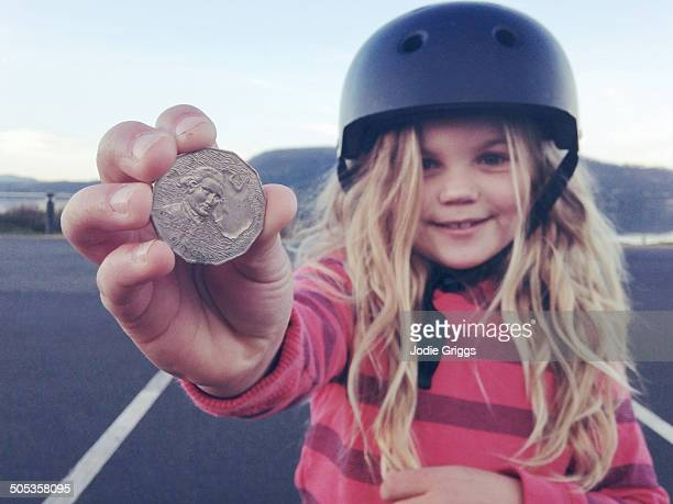 Child holding coin that she found on the ground
