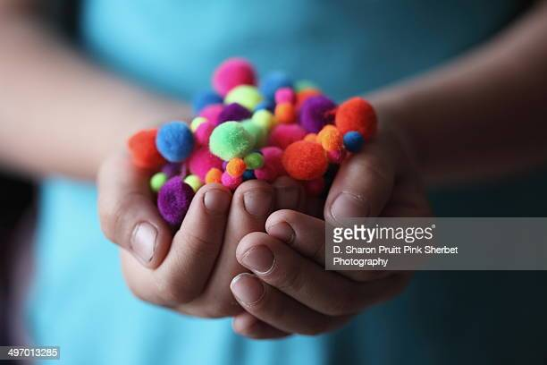 Child holding colorful fuzzy pom poms