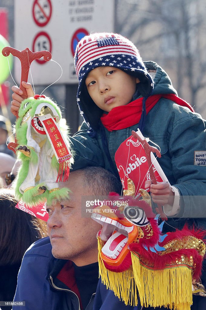 A child holding dragon-designed puppets attends a parade on February 17, 2013 in Paris as part of the Chinese New Year celebrations. Chinese communities world wide traditionally welcomed in the 'Year of the Snake'.