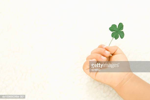Child (6-9 months) holding four leaf clover, close-up of hand
