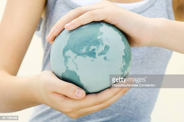 Child holding globe in hands, close-up