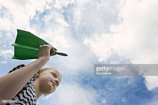 Child holding green paper aeroplane against sky