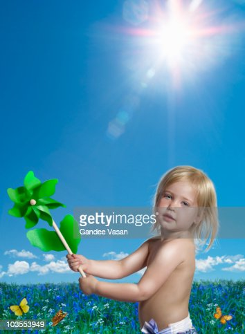 Child holding green toy windmill : Foto de stock