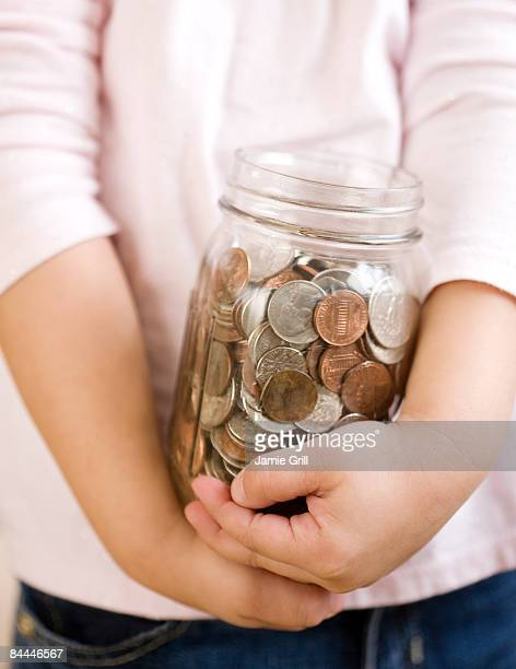 Child Holding Jar of Coins