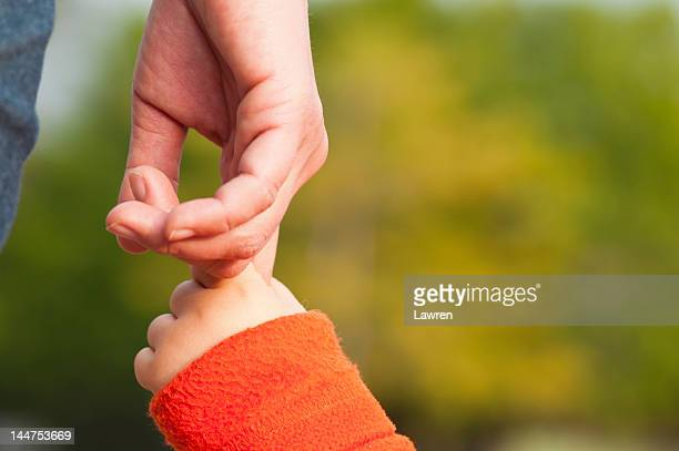 Child holding mothers hand