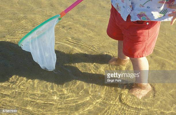 Child holding net over water