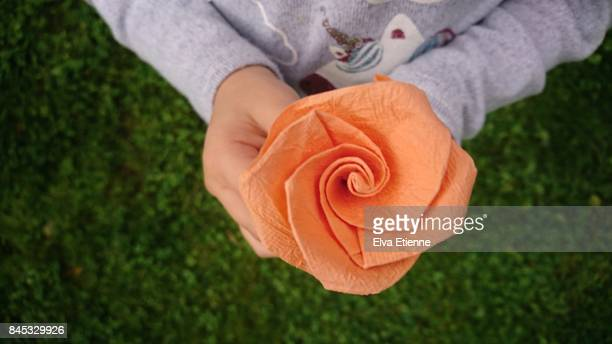 Child holding paper origami flower
