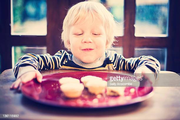 Child holding plate of mince pies