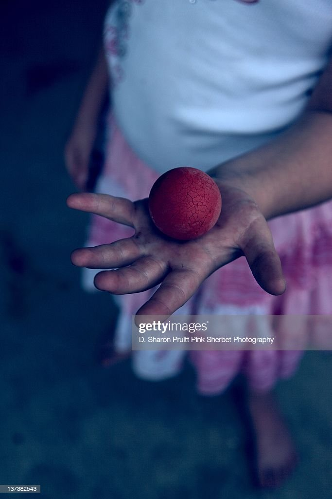 Child holding red rubber ball : Stock Photo
