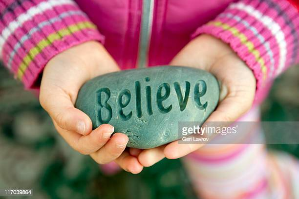 Child holding rock with carved text: Believe