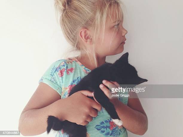 Child holding small black kitten