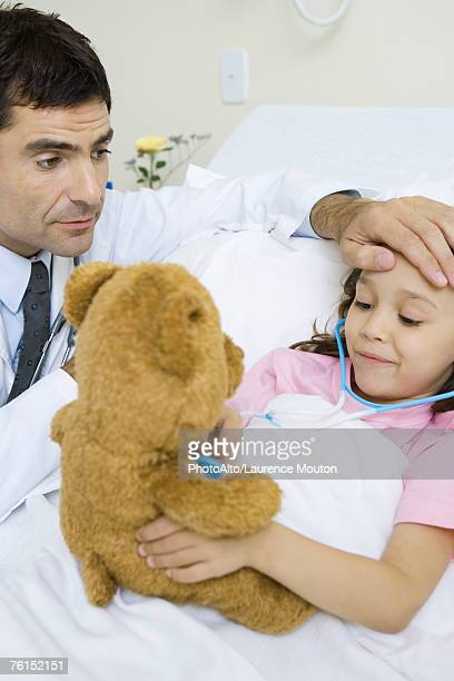 'Child holding toy stethoscope to teddy bear, doctor feeling child's forehead'