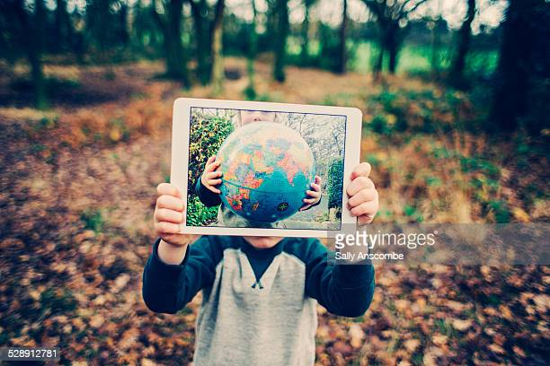 Child holding up a tablet with a globe on it