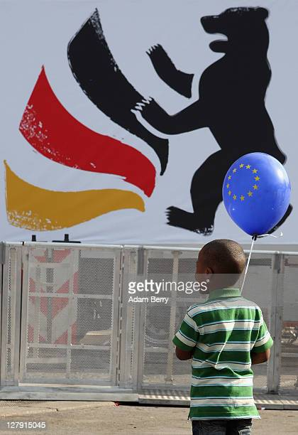 A child holds a balloon featuring the European Union flag in front of a banner with a bear the symbol of Berlin and the colors of the German flag...