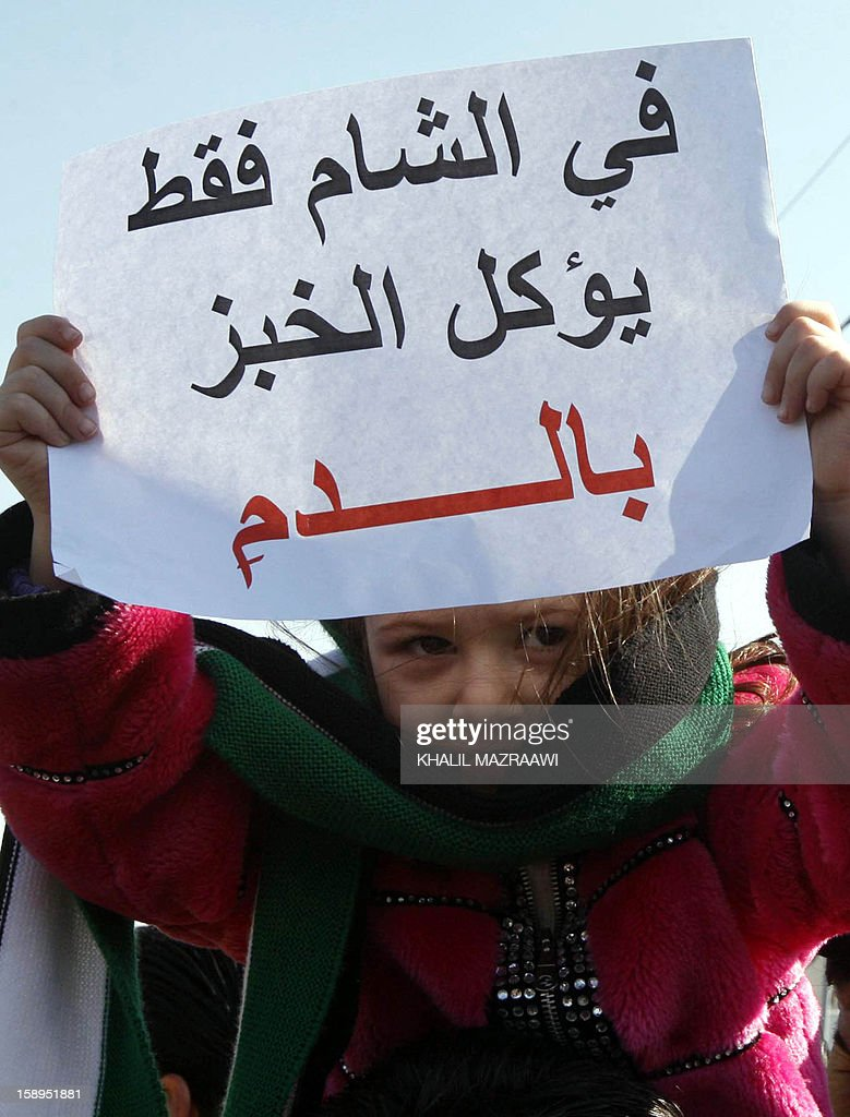'In Syria they only eat bred with blood' during a demonstration with Syrian nationals living in Jordan in solidarity with Syrians, in front of the Syrian embassy, in Amman on January 4, 2013. The protesters shouted slogans against the US and United Nations-Arab League envoy Lakhdar Brahimi. AFP PHOTO/KHALIL MAZRAAWI