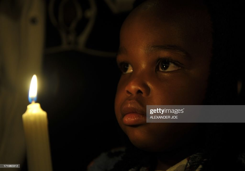 A child holds a candle as he prays for the recovery of Nelson Mandela outside the Mediclinic heart hospital in Pretoria on June 26, 2013. Mandela is receiving treatment at the Mediclinic heart hospital in Pretoria. Mandela's close family gathered yesterday at his rural homestead to discuss the failing health of the South African anti-apartheid icon who was fighting for his life in hospital. Messages of support poured in from around the world for the Nobel Peace Prize winner, who spent 27 years behind bars for his struggle under white minority rule and went on to become South Africa's first black president.