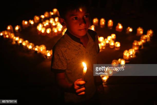 A child holds a candle in front of lamps that form the number 60 representing the 60 minutes of Earth Hour during Earth Hour in Colombo Sri Lanka...