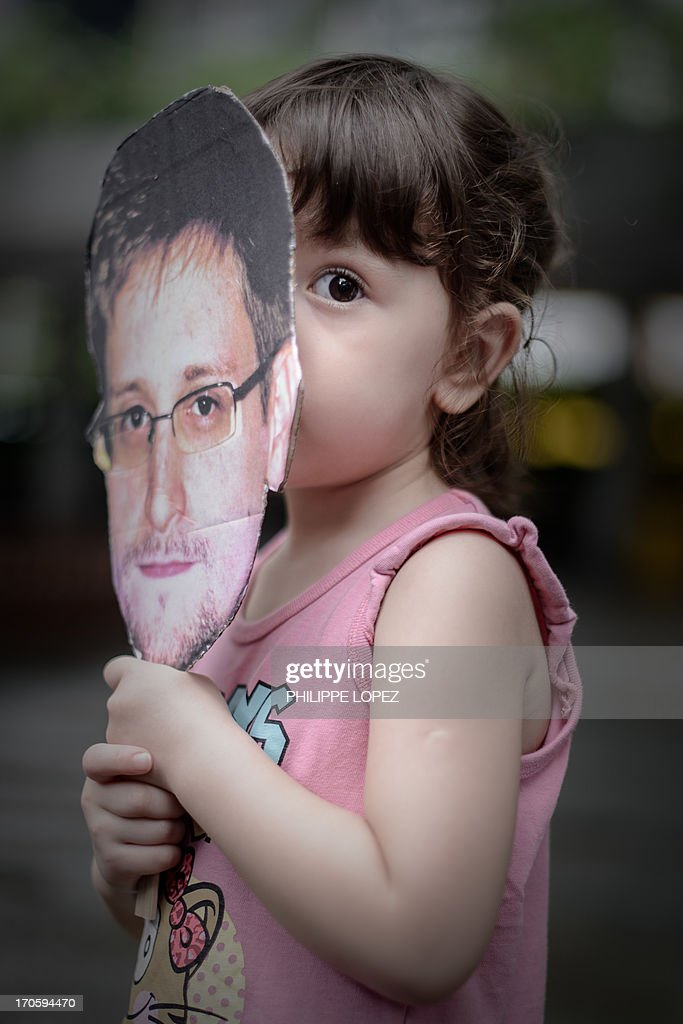 A child holds a cut out of Edward Snowden from the US during a protest in his support in Hong Kong on June 15, 2013. Snowden, a former CIA technical assistant, is in hiding in Hong Kong after he arrived in the city on May 20 and blew the lid on a vast electronic surveillance operation by the National Security Agency, which has hit targets in China and Hong Kong. AFP PHOTO / Philippe Lopez