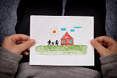 Child holds a drawn house with family. Close up.
