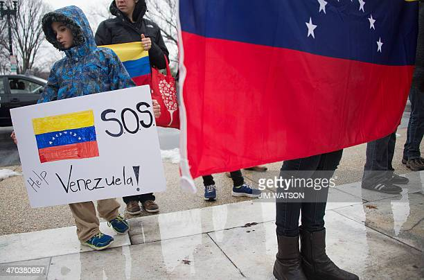 A child holds a placard among other Venezuelan protesters in opposition of the Venezuelan government in front of the Organization of American States...