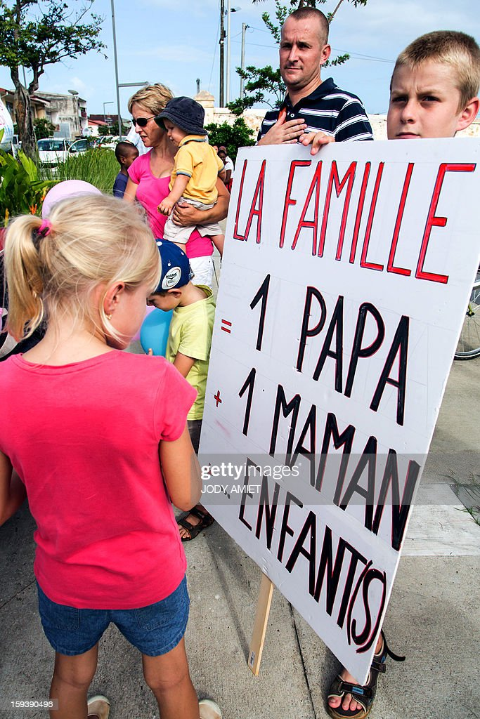 A child (R) holds a placard reading 'Family is one dad, one mom and children' during a protest against same-sex marriage, in Cayenne, in French Guiana, on January 12, 2013. Tens of thousands are set to march in Paris, on January 13, 2013 to denounce government plans to legalise same-sex marriage and adoption which have angered many Catholics and Muslims, France's two main faiths. The French parliament is to debate the bill -- one of the key electoral pledges of Socialist President at the end of this month.