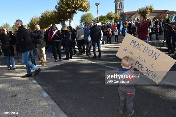 A child holds a placard reading '[French President Emmanuel] Macron give them money ' during a protest of elected representatives palmiped and...