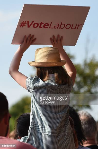 A child holds a placard reading 'Vote Labour' as she waits for Britain's main opposition Labour Party leader Jeremy Corbyn to address supporters at a...