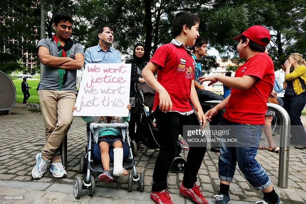 A child holds a placard reading 'We want justice, We want just this' as people take part in a demonstration in favour of Afghan refugees' rights, on August 12, 2014, in Brussels. AFP PHOTO / BELGA / NICOLAS MAETERLINCK