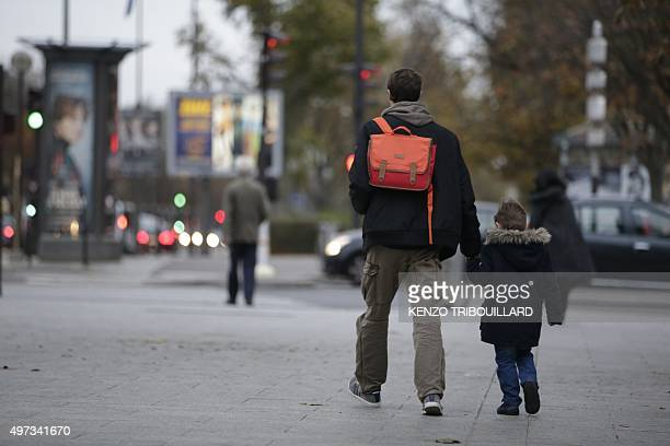 A child holds a relative's hand on his way to school early on November 16 2015 in Paris three days after the terrorist attacks that left over 130...