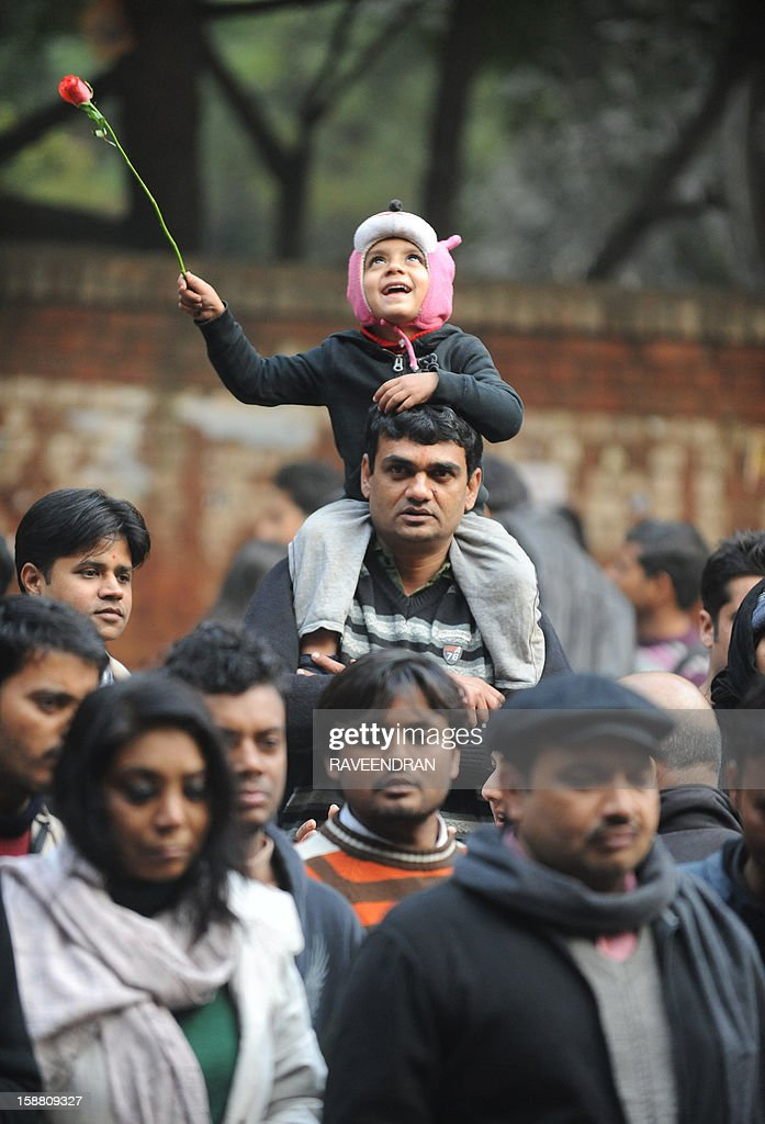 A child holds a rose on his father's shoulders on December 30, 2012 in New Delhi, during a protest rally against the gang rape of a student. The victim of a gang-rape and murder which triggered an outpouring of grief and anger across India was cremated at a private ceremony, hours after her body was flown home from Singapore. A student of 23-year-old, the focus of nationwide protests since she was brutally attacked on a bus in New Delhi two weeks ago, was cremated away from the public glare at the request of her traumatised parents.