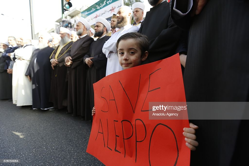 A child holds a sign reading in 'Save Aleppo' as a group of Muslim scholars protest against the air strikes conducted by the Assad regime and Russia over the Aleppo in front of Russian embassy building in Beirut, Lebanon on May 4, 2016.