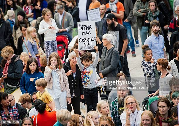 A child holds a sign reading 'open all borders now' as he takes part in demonstration in solidarity with migrants seeking asylum in Europe after...