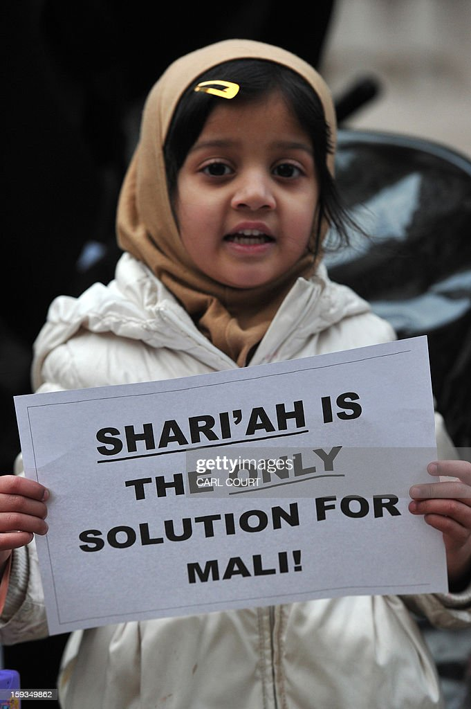 A child holds a sign that reads 'Shari'ah is the only solution for Mali' during a protest in response to French military action in Mali outside the French embassy in central London on January 12, 2013. Around 50 Muslim protesters shouted slogans and waved signs as they demonstrated outside the French embassy against French intervention in Mali. France sent troops on January 11 to help Malian forces hold back a rebel advance towards the capital Bamako, and on January 12 Paris announced that a French military pilot had been killed. AFP PHOTO / CARL COURT