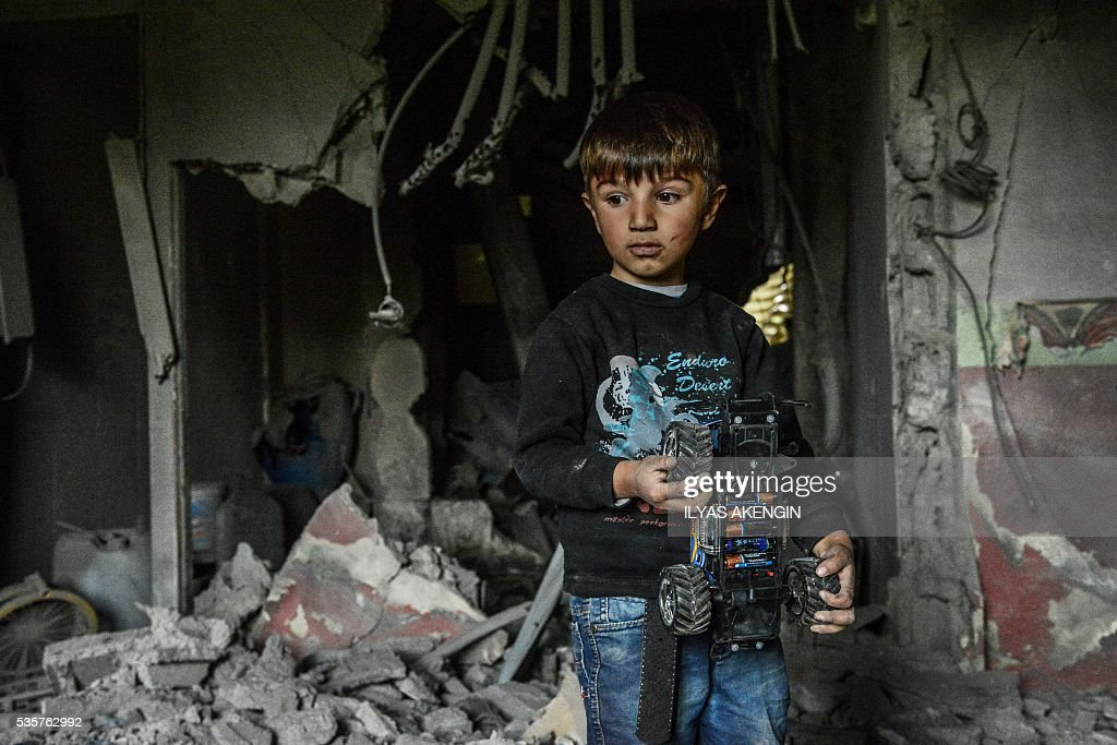 A child holds a toy as he stays inside a damaged house following heavy fightings between government troops and Kurdish fighters after the curfew on May 30, 2016 in the majority Kurdish city town of Yuksekova, southeastern Turkey near the border with Iraq and Iran. / AFP / ILYAS