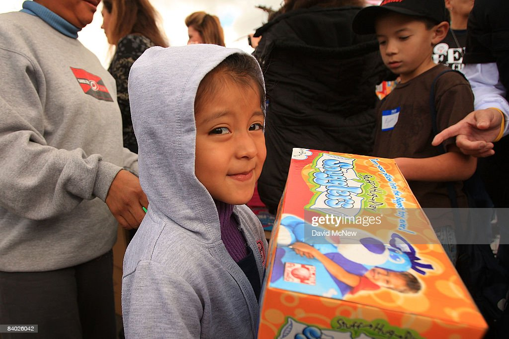 A child holds a toy as people receive gifts of food, personal care and household items and toys at the Miracle in South Central event, part of the nationwide Miracle on Main Street, USA program to help working poor and disadvantaged families on December 13, 2008 in the South Central neighborhoods of Los Angeles, California. About 5,000 families are expected to receive enough food at the event to supplement meals for a family of four for a week. Miracle on Main Street, USA is sponsored by The National Basketball Players Association (NBPA) along with Feed The Children, Feed 333, Humanity Unites Brilliance (HUB) and hosted by the Salvation Army.