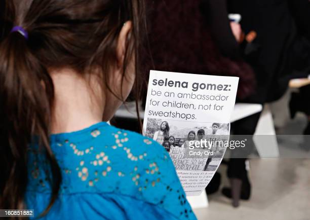 A child holds a USAS flyer at the adidas NEO Label Fall 2013 fashion show on February 6 2013 in New York City