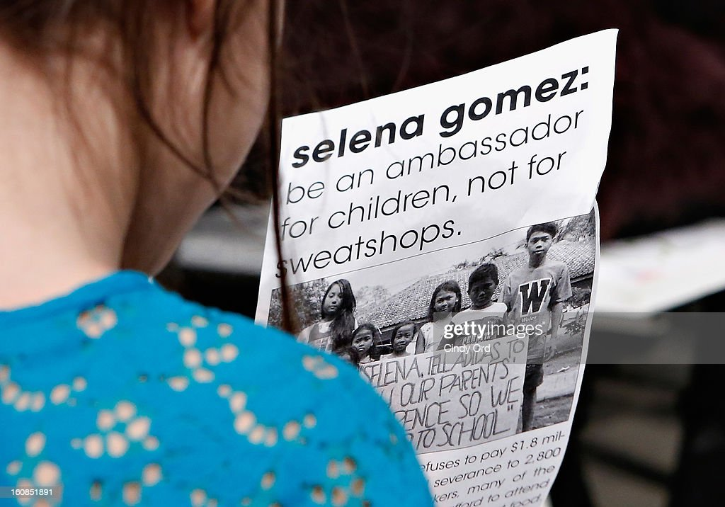 A child holds a USAS (United Students Against Sweatshops) flyer at the adidas NEO Label Fall 2013 fashion show on February 6, 2013 in New York City.
